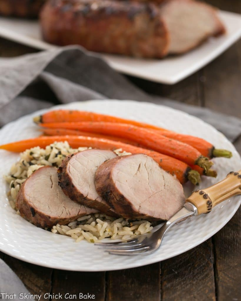 Whiskey Marinated Pork Tenderloin served on a white plate with carrots and rice