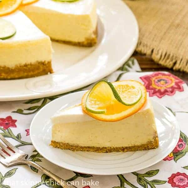 Margarita Cheesecake slice garnished with a slice of orange and lime on a white plate