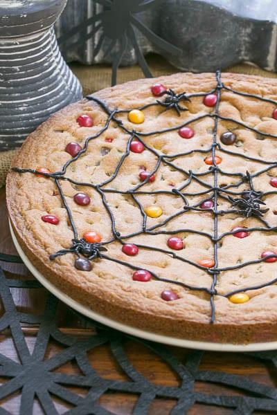 Spiderweb Cookie Cake on a white plate over a black felt spiderweb