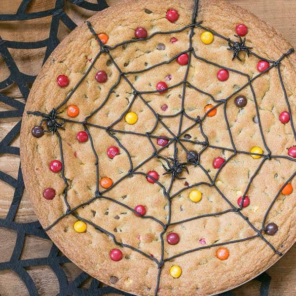 Spiderweb Cookie Cake topped with M&M's on a felt spiderweb