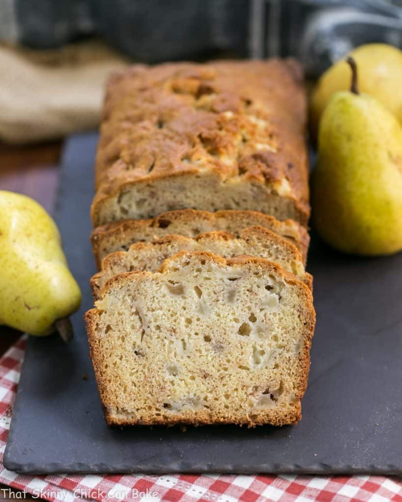 Sliced Sour Cream Pear Bread with whole pears on a slate tray