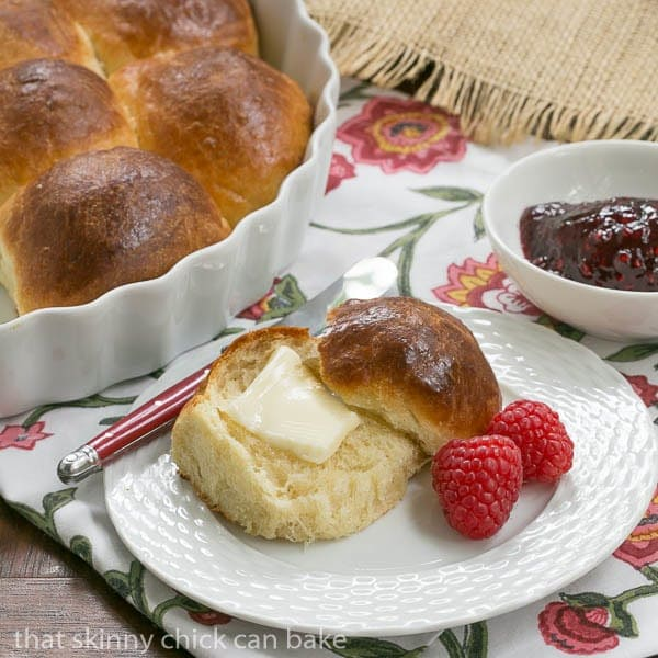Brioche Dinner Rolls on a white plate with a pat of butter