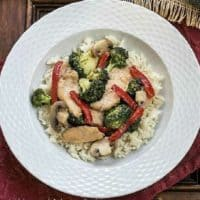 Chicken, Broccoli and Bell Pepper Stir Fry in a white bowl over a burgundy napkin
