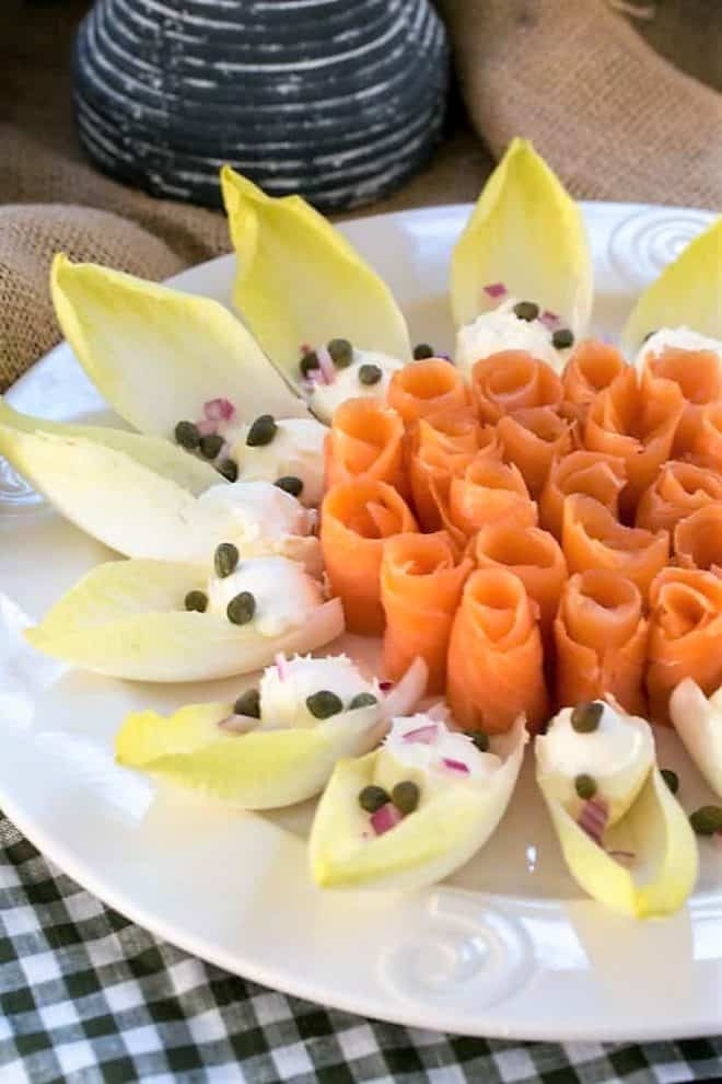 Smoked salmon roses- arranged on a white serving plate with endive, creme fraiche, capers and red onion