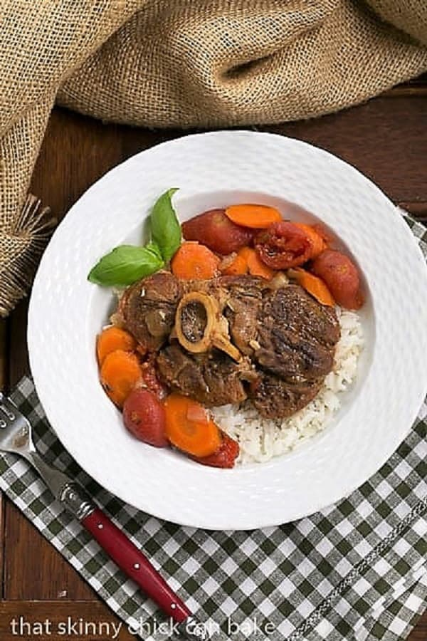 Osso Buco a L'arman in a white bowl over a green and white checked napkin