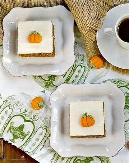 Killer Pumpkin Bars with Cream Cheese Frosting on square white plates with a cup of tea