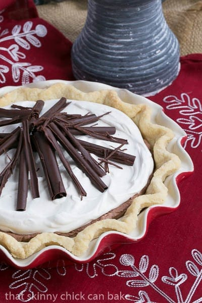 Uncut Black Bottom Chocolate Mousse Pie in a red pie plate with chocolate curl garnishes