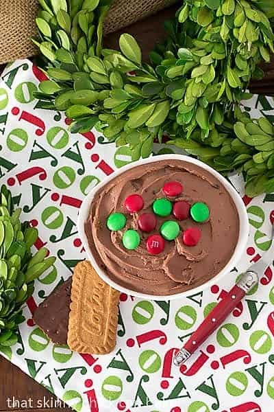 Brownie Batter Dip on a holiday napkin with cookies and a red handled serving spoon