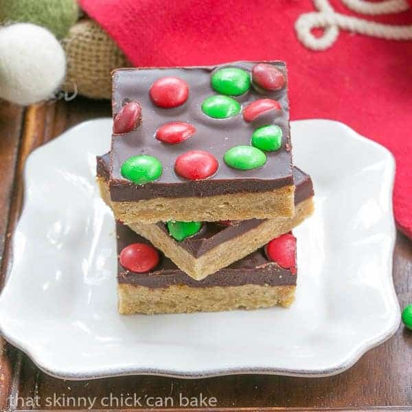 Candy Topped Toffee Squares stacked on a square white plate