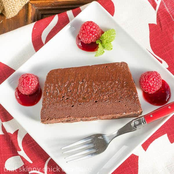 Slice of Chocolate Terrine with Raspberry Sauce on a square white plate