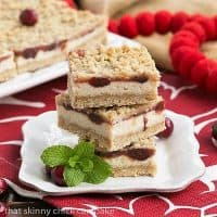 A stack of 3 cranberry cheesecake bars on a square white plate
