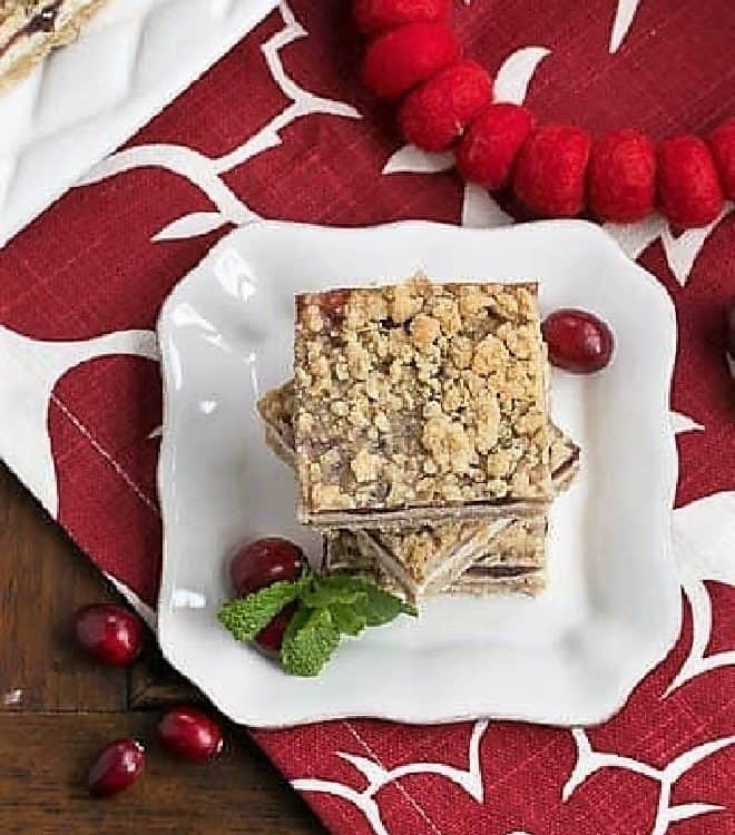 Cranberry Cheesecake Bars on a white dessert plate with fresh cranberries and mint