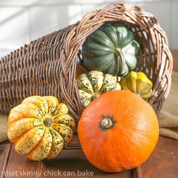 Red Kuri Soup squash along with other varieties in a wicker cornucopia