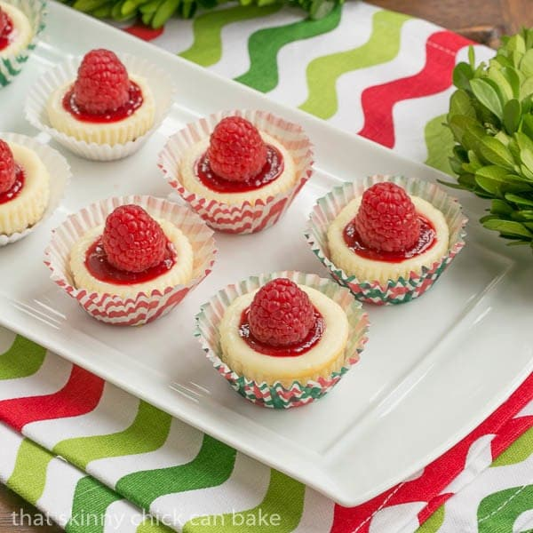 Mini Mascarpone Cheesecakes on a white tray topped with raspberry sauce and raspberries