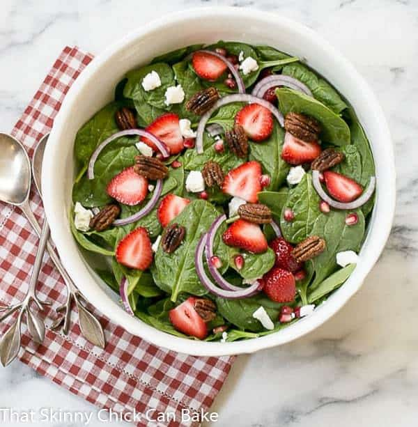 Spinach, Strawberry, Pomegranate, Feta Salad in a large white salad bowl on a red and white checked napkin