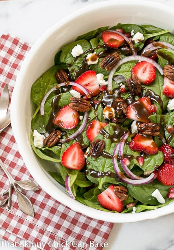 Spinach, Strawberry, Pomegranate, Feta Salad drizzled with a vinaigrette in a white ceramic serving bowl