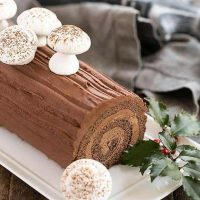 Bûche de Noël garnished with meringue mushrooms and holly