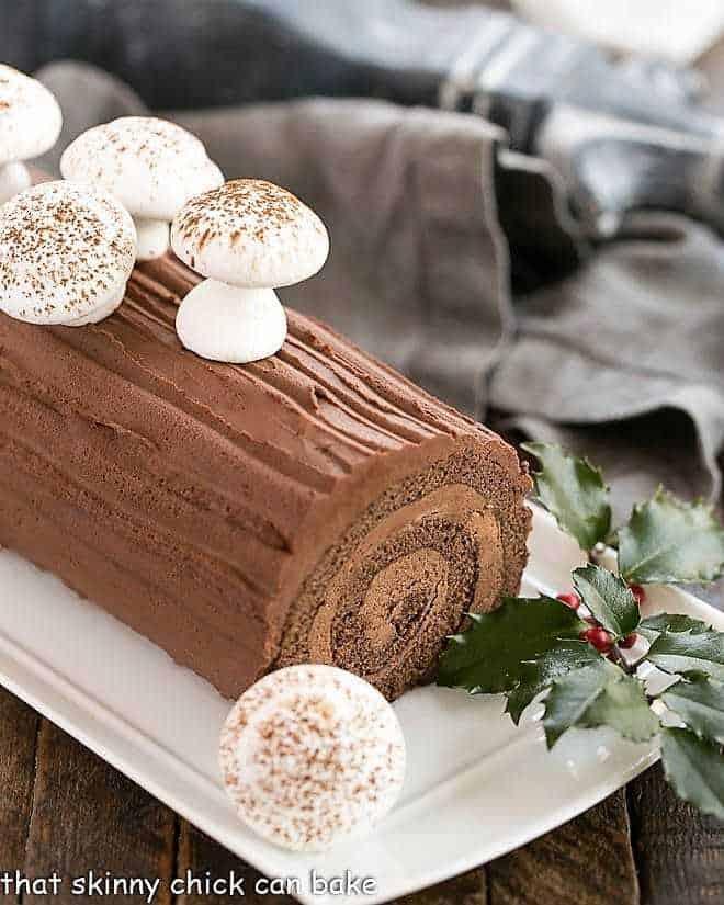 Bûche de Noël garnished with meringue mushrooms and holly