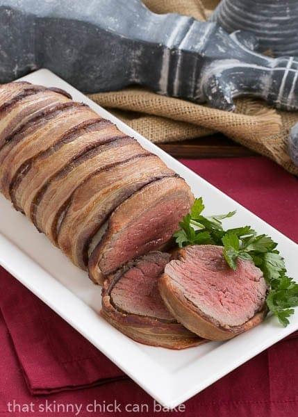 Beef Tenderloin with Gorgonzola Sauce wrapped in bacon on a white platter