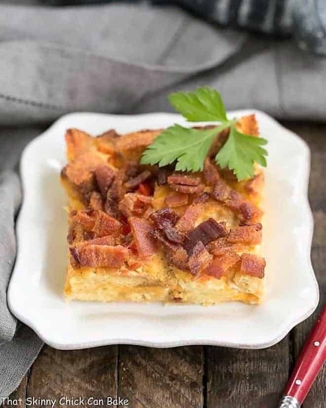 Bacon and egg strata slice on a small white plate
