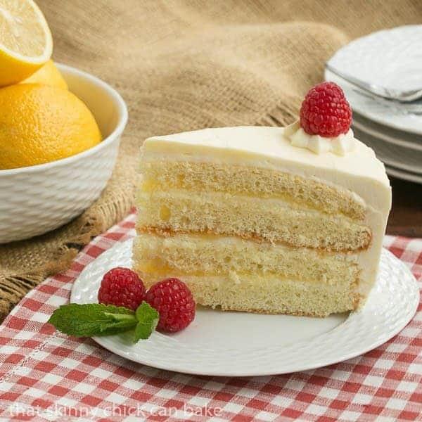 Slice of Lemon Mascarpone Layer Cake on a white plate garnished with raspberries