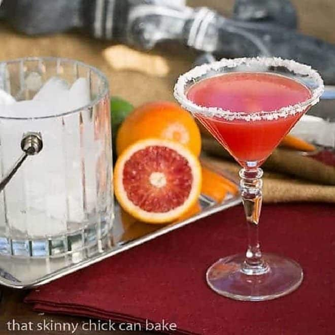 Blood Orange Margaritas in stemmed cocktail glass in front of oranges and a crystal ice bucket