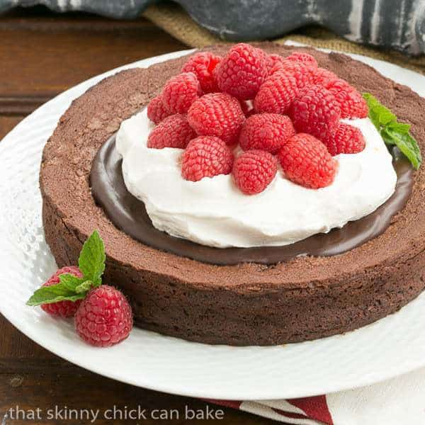 Chocolate Earthquake Cake  on a white plate topped with chocolate, cream and berries