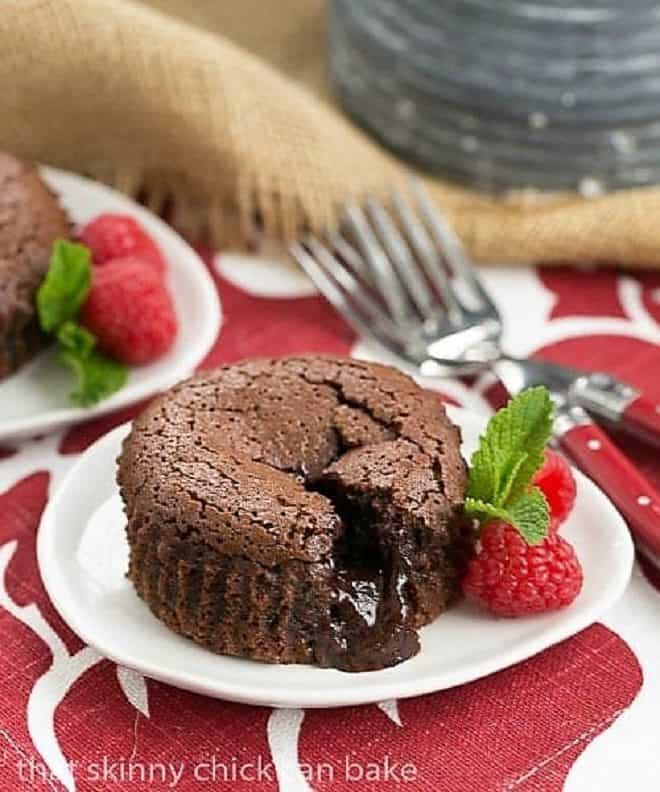 Chocolate Lava Cakes broken open with the fudgy centers exposed on a white dessert plate