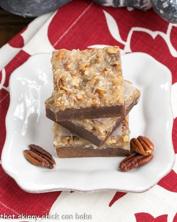 German Chocolate Brownies on a square white plate with pecan halves