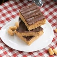 Homemade Reese's Bars stacked on a white plate on a red and white checked napkin
