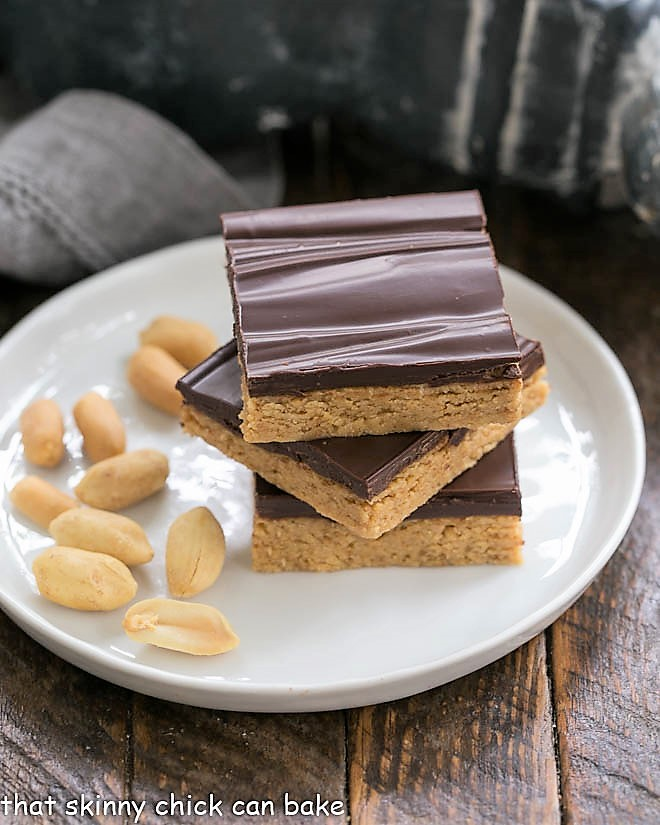 Homemade Reese's Bars stacked on a roung plate with shelled peanuts
