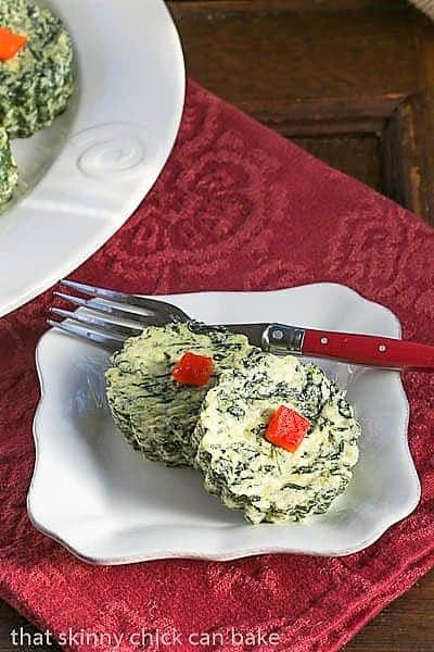 Mini Spinach Souffles on a white plate with a red handled fork