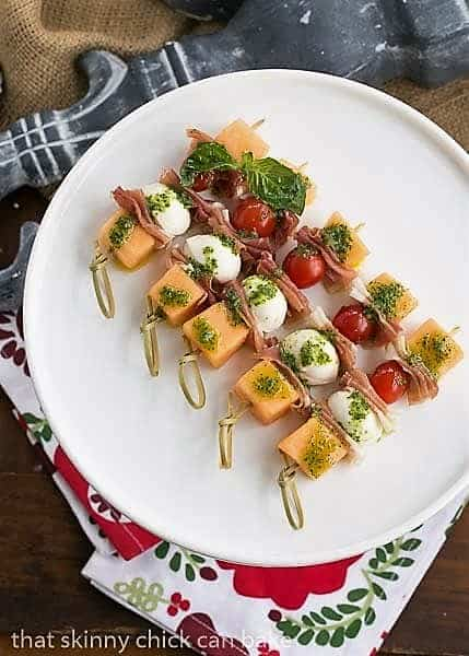 Melon and Prosciutto Skewers lined up on a white cake stand