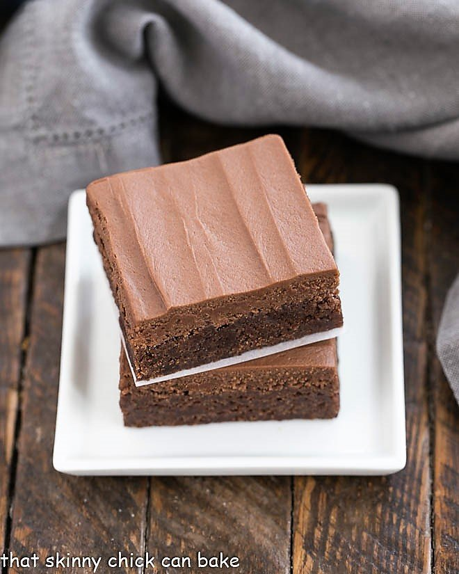 Frosted Brownies Recipe stacked on a small white plate