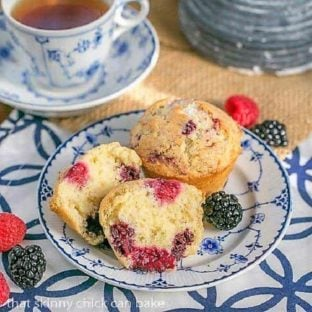 Double Berry Muffins on a blue and white plate with a cup of tea