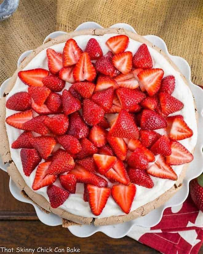 Strawberry Topped Chocolate Pavlova overhead shot on a ruffled white cake plate