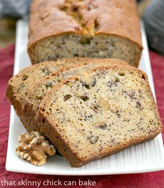 Classic Banana Walnut Bread on a white ceramic tray garnished with walnuts