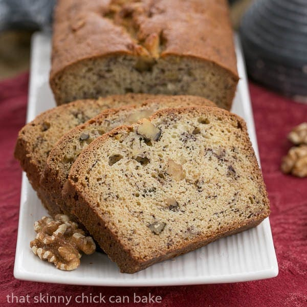 A loaf of banana nut bread and slices on a white tray