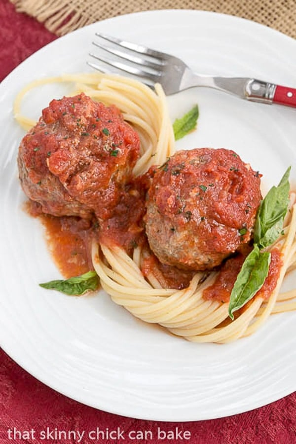 Mozzarella Stuffed Meatballs with pasta on a white plate