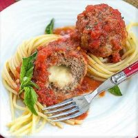Mozzarella Stuffed Meatballs intertwined with spaghetti and garnished with basil