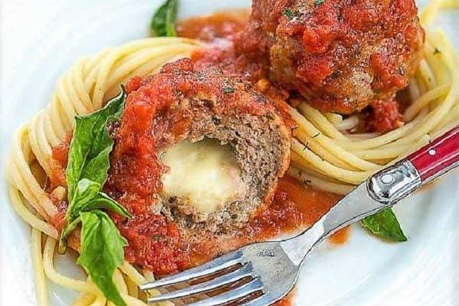 Mozzarella Stuffed Meatballs intertwined with spaghetti and garnished with basil