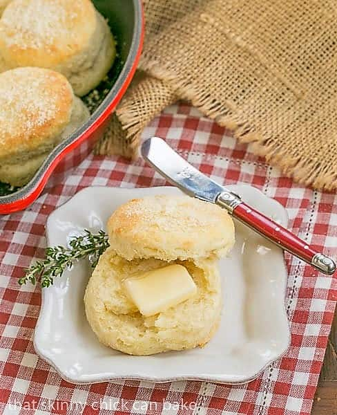 Buttermilk Goat Cheese Biscuits with a pat of butter on a square white plate and a red handle knife