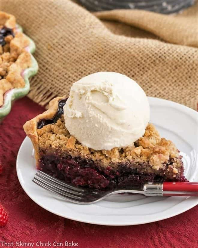 Razzleberry Pie or Triple Berry Pie slice topped with ice cream on a white plate
