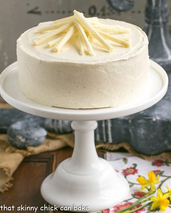 White Birthday Cake topped with white chocolate curls on a cake stand