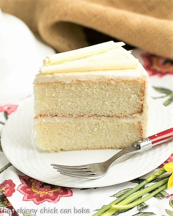 White birthday cake slice on a white plate over a floral napkin