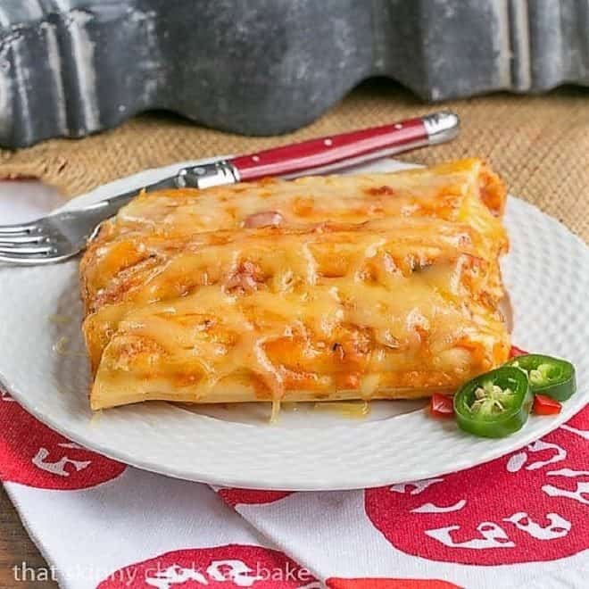 Mexican Chicken Manicotti on a white basket weave plate with a red handled fork