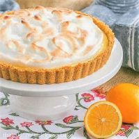 Meyer Lemon Tart with Meringue Topping on a white cake stand next to Meyer lemons