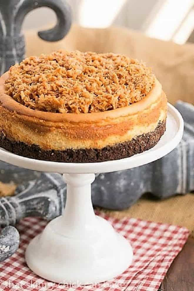 Samoa Cheesecake with a Coconut Caramel Topping on a white cake stand