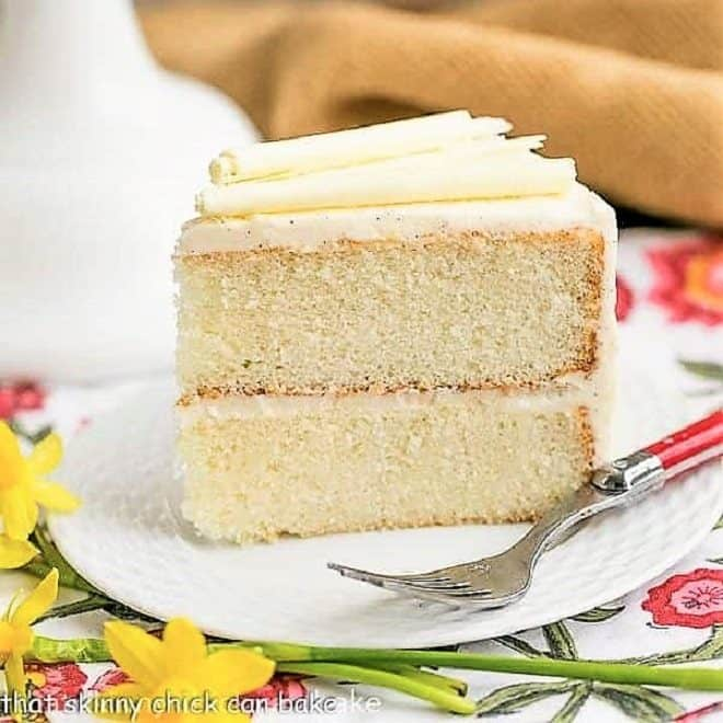 White Birthday Cake slice on a white plate with a red handle fork