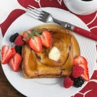 Overnight Cinnamon Bread French Toast on a white plate topped with berries